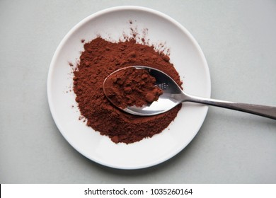 Cocoa spoon, ingredient. Pile of cocoa powder in metall spoon isolated on white plate. Top view.