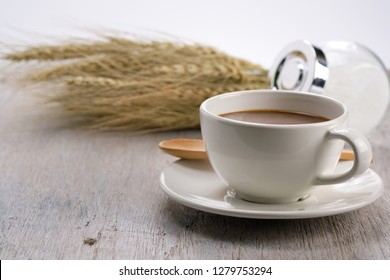 Cocoa in white cup on wooden table with malt and sugar . - image
