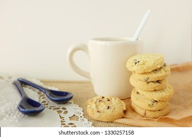 Cocolate chip cookies with a tea spoon on brown and white background.A ceramic cup of milk and bakery natural food concept style.