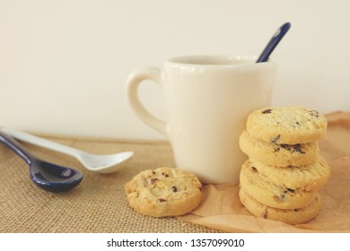 Cocolate chip cookies with a tea spoon on soft brown and white background.A ceramic cup of milk and bakery natural food breakfast concept style.