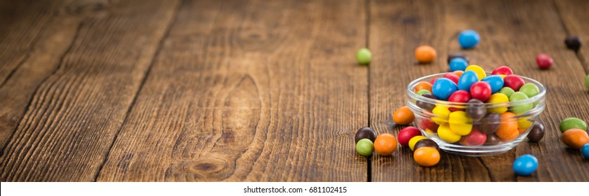 Cocolate coated Peanuts on an old wooden table as detailed close-up shot (selective focus)