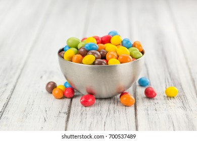 Cocolate coated Peanuts on rustic wooden background (close-up shot)