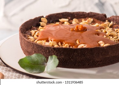 Cocolate tart with peanuts and caramel on the white wooden background