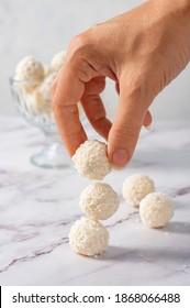Coconut balls, ehite chocolate rafaello candies. Vegetarian round tasty dessert, hand holding a ball