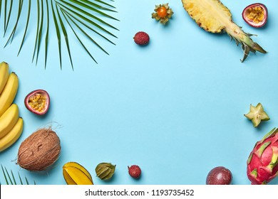 Coconut, banana, carambola, physalis and green palm leaf on a blue background with copy space. Creative Food frame. Flat lay