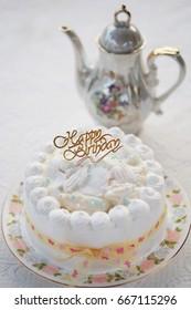Coconut birthday Cake with tea pot on white background