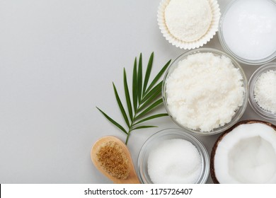 Coconut body scrub with ingredients on gray table top view. Homemade cosmetic for peeling and spa care. Flat lay.