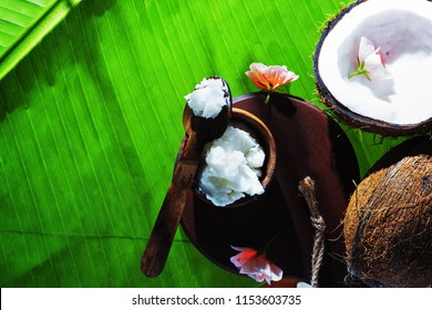 Coconut butter oil with flowers  on banan leaves. Spa concept.Text space.