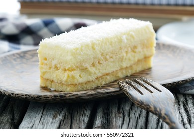 Coconut cake on wooden plate.