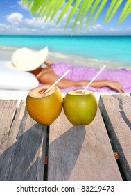 coconut cocktails with a woman sun tanning in topical Caribbean beach [Photo Illustration]