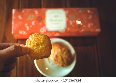 Hand holding traditional baked coconut cookie on blurry background. Texture of traditional coconut cookies close up and copy space for text. Homemade bekery concept.