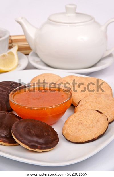 "Coconut cookies ""buttons"" on a white plate with a serving of tea drinking tea with jam"