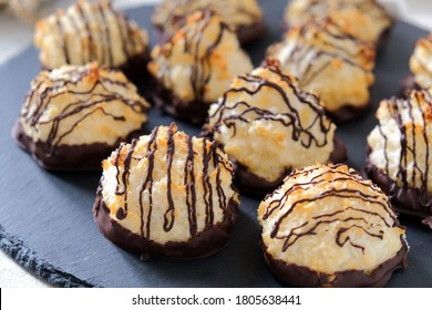 Coconut cookies in chocolate on a black plate. Close up.