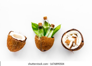 Coconut cosmetics. Organic oil in small bottles on white background top-down