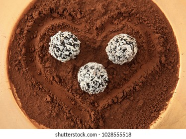 coconut covered chocolate truffles on cacao background with heart shape