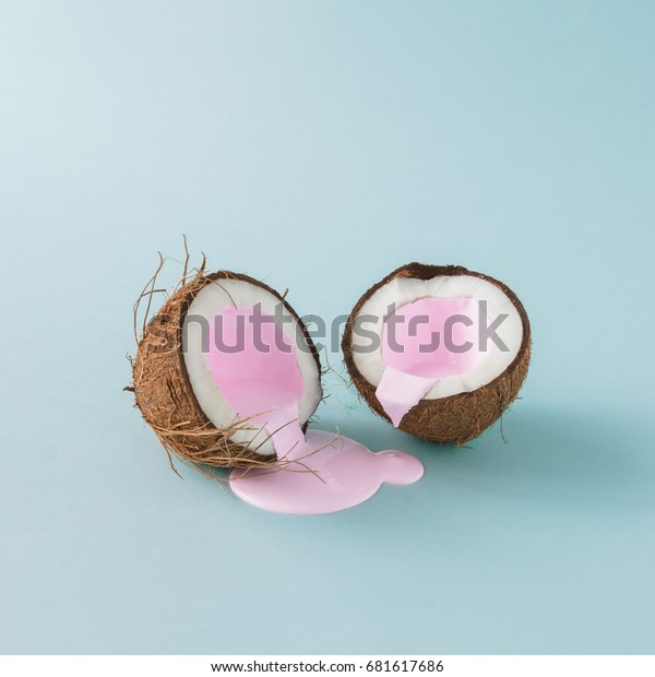 Coconut cracked in half with pink milk pouring. Minimalism. Food creative concept.
