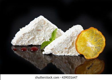 coconut cream dessert with sweet sauce decorated with dried orange slice on black background