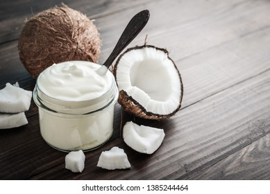 Kokoscreme in einem Glas mit frischer Kokosnuss auf Holzhintergrund.  Gesundes veganisches Lebensmittelkonzept.