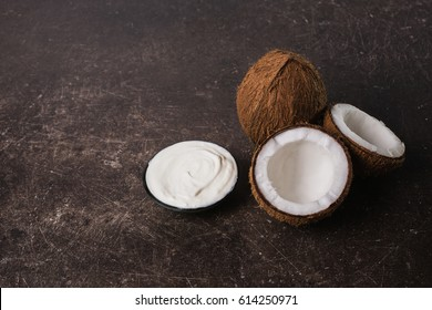Coconut, cream, coconut milk and oil on a dark marble background. Personal care. Spa treatments