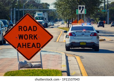 Coconut Creek, Florida, USA - February 05, 2021: Police car staying on the road with lights for traffic control in road work zone.