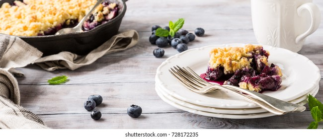 Coconut crumble on white plate with fresh apples and blueberry. Healthy food concept. Banner.