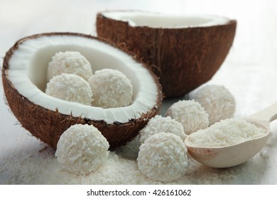 coconut cut into pieces  with candy in coconut chips on a white wooden background
