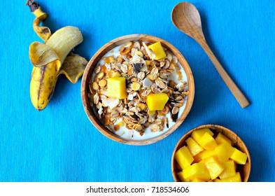 Coconut & dark chocolate muesli with coconut yogurt, banana and fresh mango chunks.