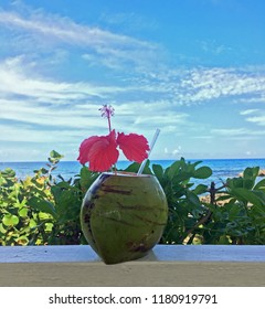 Coconut Drink adorned with red hibiscus flower on white railing in tropical scene