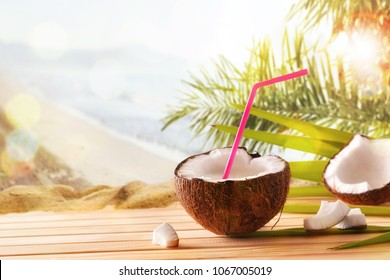 Coconut drink in coconut fruit on wooden table on tropical beach background. Alternative milk concept. Front view. Horizontal composition.