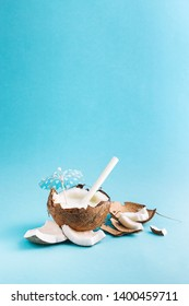 Coconut drink served in it`s shell with a small blue umbrella and a white paper straw. Parts of it`s shell with coconut meat are arranged next to the drink.