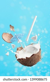 Coconut exploding open revealing its fresh milk and meat. It burst open and is ready to be served with the big straw and an cocktail umbrella, flying through the droplets of coconut milk