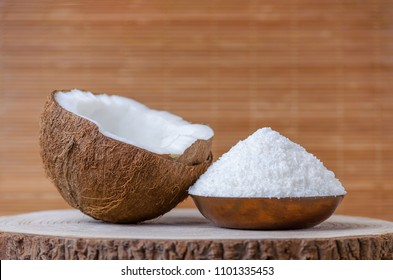 coconut flakes in a bowl on brown wooden background