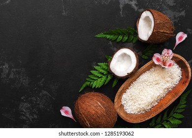 Coconut and coconut flakes in a wooden bowl on a dark concrete background are decorated with fern leaves and pink alstroemeria flowers. Top view, copy space