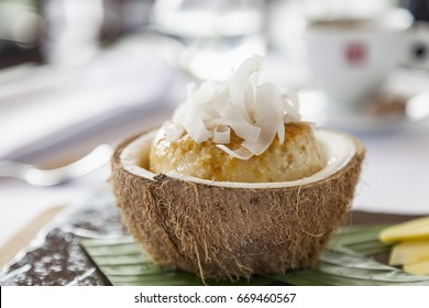 Coconut flan in coconut shell, with pineapple, coffee and pink flowers on the background horizontal