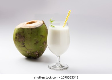 coconut flavored plain white lassi OR milk shake garnished with a coconut and mint leaves. Selective focus