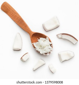 Coconut flesh in wooden spoon and pieces of coco on white background, copy space.