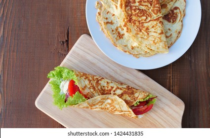 Coconut flour and psyllium husk keto wrap with bacon, tomatoes and lettuce. Low-carb gluten free tortillas on cutting board and plate over wooden table.