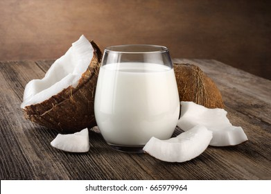 Coconut and a glass of coconut milk on a wooden background. Healthy food.