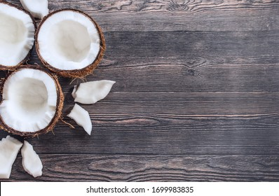 coconut halves, coconut pieces on a wooden background top view. background with split coconuts close-up. coconuts and copy space. coconuts lay flat.