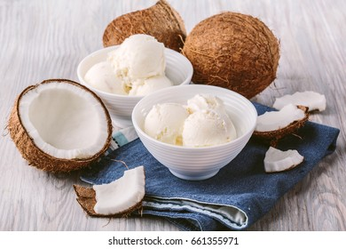 coconut ice cream in a white bowl on a wooden background