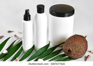 Coconut with jars of coconut oil and cosmetic cream on white background