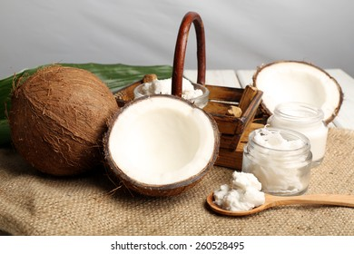 Coconut with jars of coconut oil and  cosmetic cream on sackcloth on light background