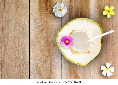 Coconut juice with flower on wooden table,Top view.