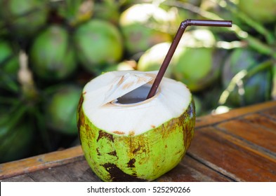 Coconut juice on wood table in blurred  Coconuts background.