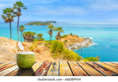 Coconut juice on wood table with Phromthep cape, beautiful andaman sea view in Phuket island in summer, Summer holiday concept