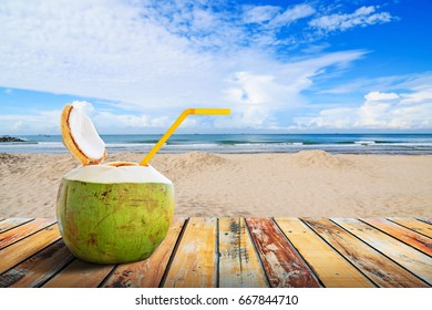 Coconut juice and straw on wood table in summer with blurred beach background , Summer holiday concept