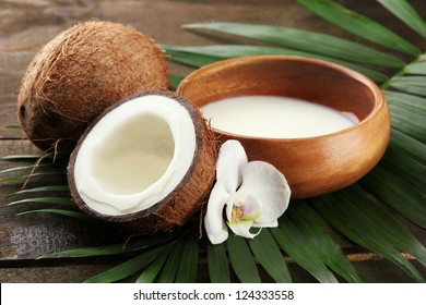 Coconut with leaves and flower, on grey wooden background