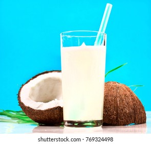 Coconut with leaves and milk in a glass isolated on cyan background.