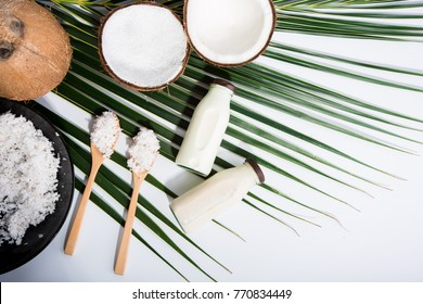 coconut milk in bottles and fresh coconut on green leaves , white background top view with copy space