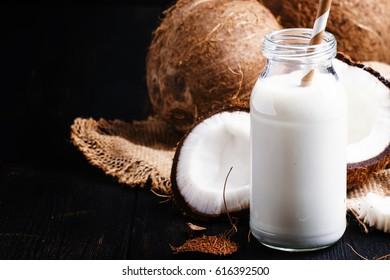 Coconut milk in a glass bottle, dark background, selective focus
